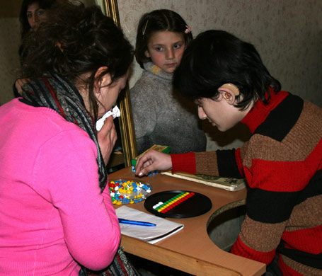 A deaf child working with a World Vision staffer
