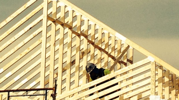 A worker properly spaces and secures the trusses.