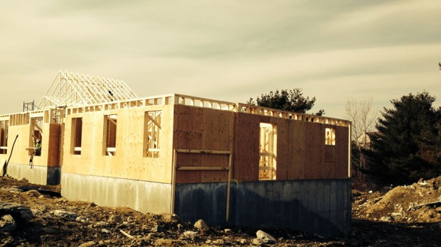 Wood framing is being built on the concrete foundation.