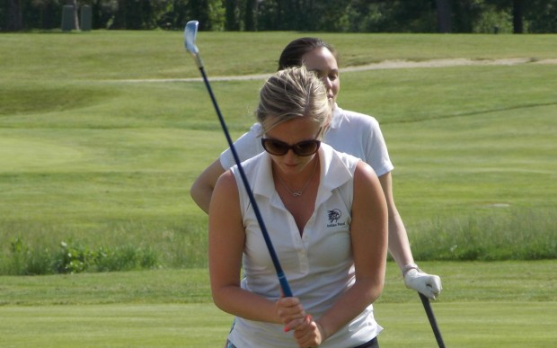 Woman sets up next golf shot to get onto the green.